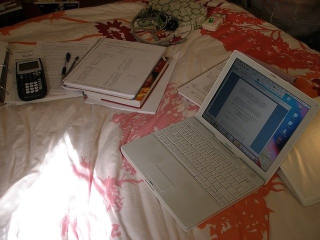 Photo of a laptop and notebooks on a bed